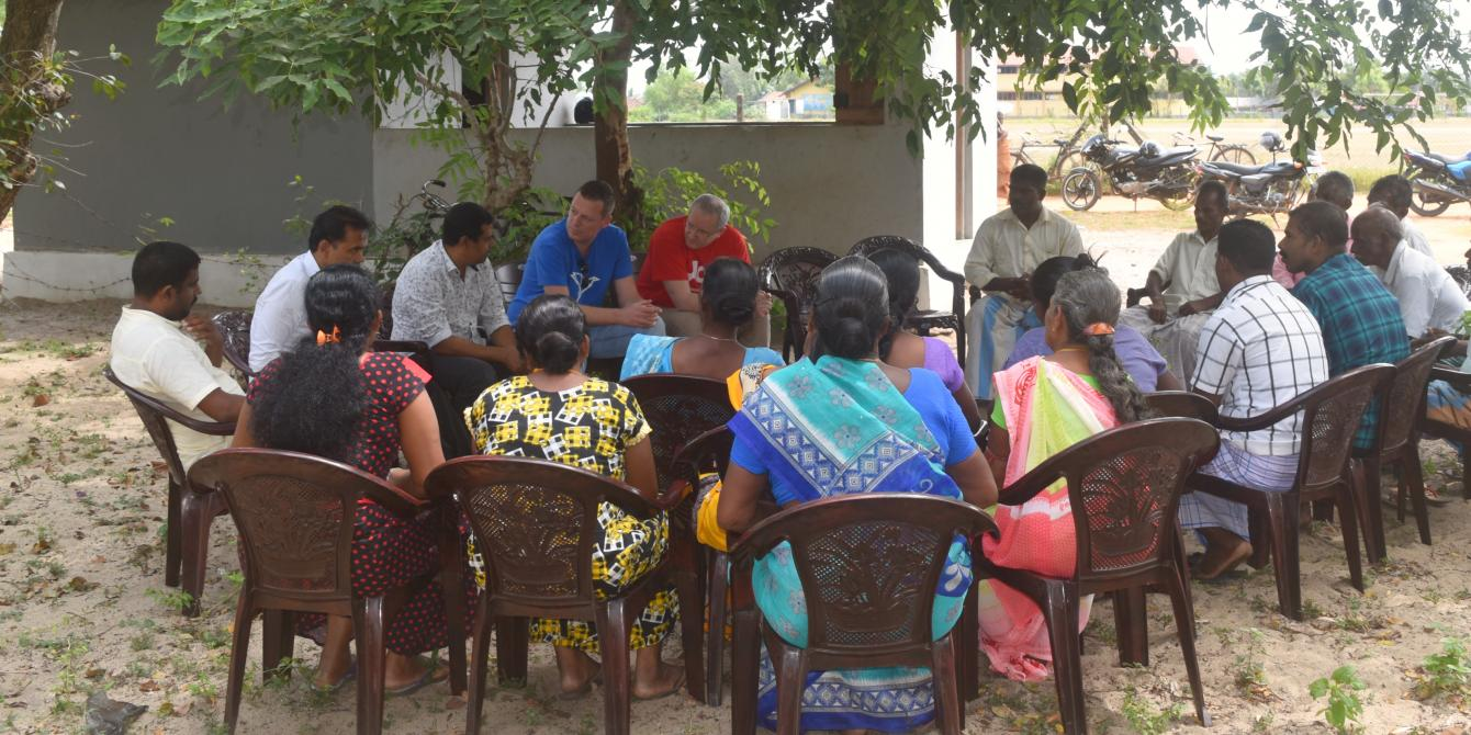 Farmers seated outside in discussion with Oxfam and partners